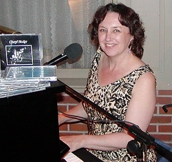 "Cheryl Hodge at the piano, next to her first CD, entitled ""Tonight I'm Wearing Basic Black"""